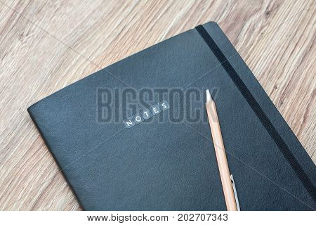 Closed classic planner with pen is on a wooden desk. Nothing extra