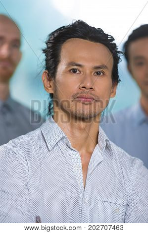 Serious confident Asian male executive with stubble looking at camera. Confident handsome middle-aged businessman running company. Business portrait concept