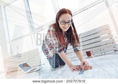 Important scheme. Woman standing on her knees while drawing lines on a big scheme