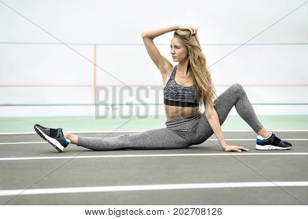Sportive girl sits on the twine on the cycle track outdoors. She holds her right hand on the hair and looks to the side. Her left leg is bent in the knee. Girl wears gray sportswear and dark sneakers.