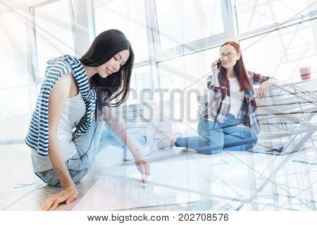 Very talented. Concentrated hard working designer making a new masterpiece while her smiling colleague talking on the mobile phone