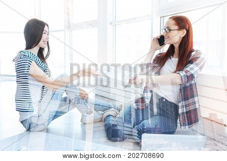 Take a look. Two positive young colleagues holding a new business plan and talking on the phone while sitting on the floor and looking at each other