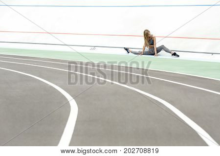 Pretty girl sits on the twine on the cycle track outdoors. She holds her hands on the ground and looks downward. Her left leg is bent in the knee. Girl wears a gray sportswear and dark sneakers.