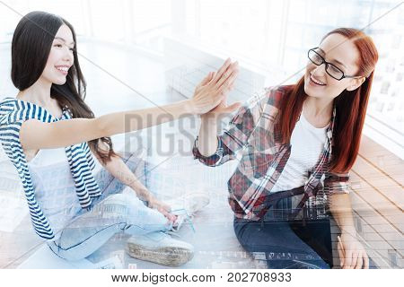 Being optimistic. Close up of beautiful splendid girls keeping hands together while being happy and joyful