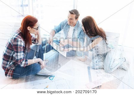 Look here. Hardworking workers full of enthusiasm discussing important tasks and expressing their opinion while pointing at the document