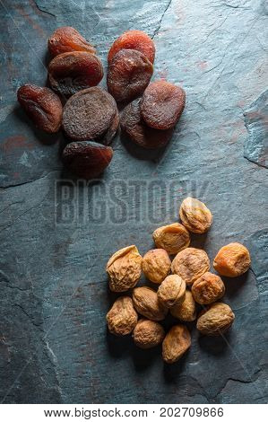 Yellow and brown dried apricots on a blue gray stone vertical