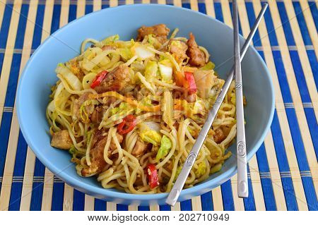 Bami goreng, fried noodles with cabbidge, soja sauce, chili pepper, pork in a blue ceramic bowl on a striped wooden carpet