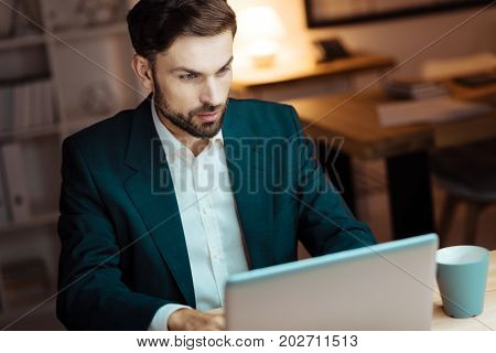 Young businessman. Very attentive brunette man raising eyebrows and looking forward while working at his project