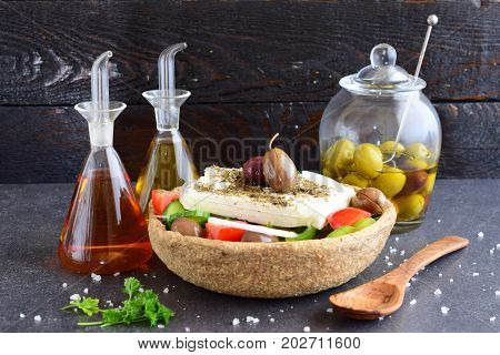 Traditional greek salad with cucumber, onion, tomato, paptika, feta cheese, olive oil and oregano in a eatable bowl made of a special traditional rye dough with glass jars with olive oil , vinegar and olives on an abstract background. Healthy eating conce