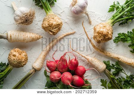 Background of celery roots, parsley, radishes with leaves and garlic on white table horizontal