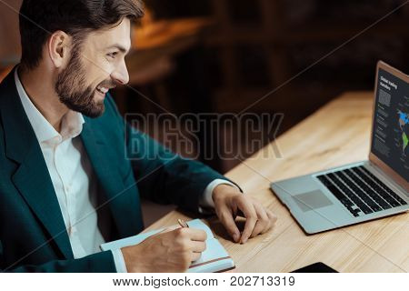 Joyful mood. Attractive brunette sitting in semi position and keeping smile on his face while looking at laptop