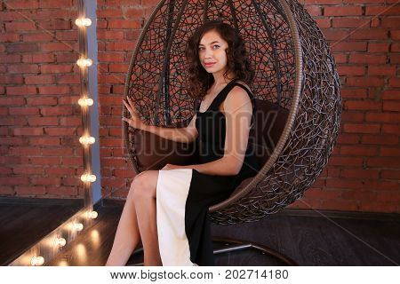 Beautiful girl in black evening dress sitting in the round rattan chair. Supermodel, indoor