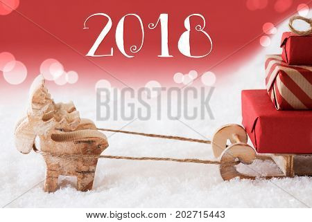 Moose Is Drawing A Sled With Red Gifts Or Presents In Snow. Christmas Card For Seasons Greetings. Red Christmassy Background With Bokeh Effect. English Text 2018 For Happy New Year
