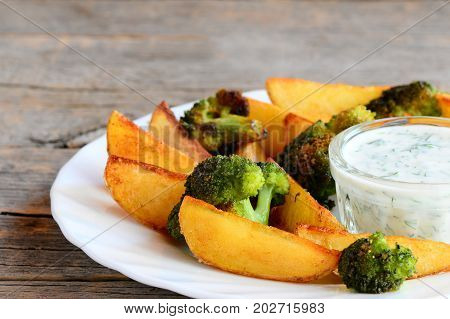 Roasted potatoes slices and broccoli florets with dill sour cream sauce on a plate and a wooden table. Simple potatoes and broccoli recipe idea. Rustic style. Closeup