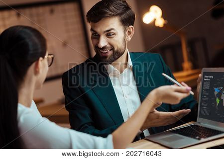 Always smile. Delighted brunette expressing positivity and raising eyebrows while talking to his partner