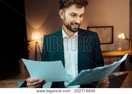 Let me look. Young professional manager expressing positivity and bowing head while looking at documents