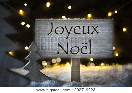 Sign With French Text Joyeux Noel Means Merry Christmas. White Christmas Tree With Snow And Magic Glowing Lights In Backround. Card For Seasons Greetings.