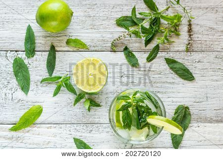 Mojito Cocktail With Lime And Mint In Highball Glass On A White Wooden Background Top View