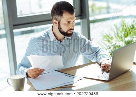 Careful examination. Handsome bearded man sitting in the office and checking the data on the printouts, looking it up on the laptop