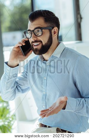 Heated discussion. Young bearded man talking on the phone and arguing with his colleague, making objections to his opinion