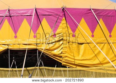 Exterior of a yellow and pink circus tent