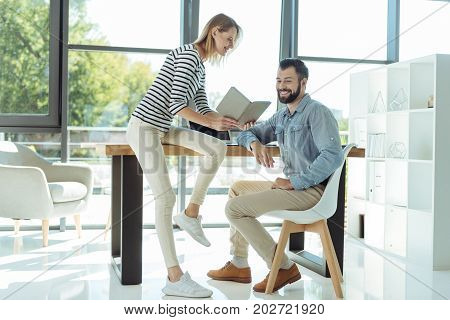 Planning time together. Pretty young woman sitting on the table in the sun-drenched office and discussing with her male colleague their schedule, showing him a daily planner