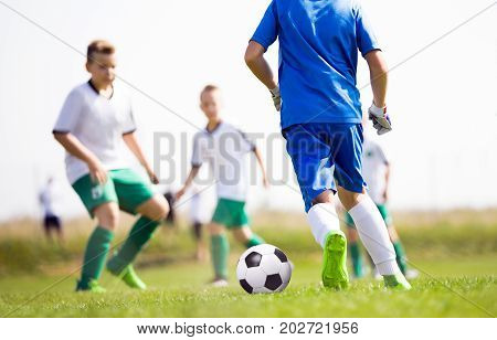 Young boys playing football soccer game on sports field. Kids running after the soccer ball. Children kicking football match