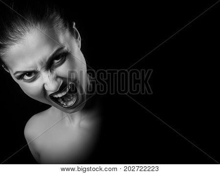 angry nude girl screaming at camera on black background with copy space, monochrome