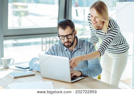 Helpful advice. Charming young woman pointing at the laptop screen and suggesting new idea to her male colleague working on a new company project