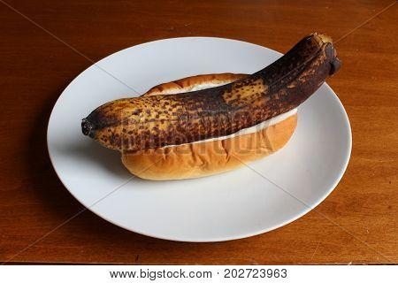 Unpeeled banana in a bun with mayonnaise