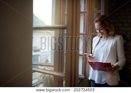 Smile blonde woman in company calling business partner