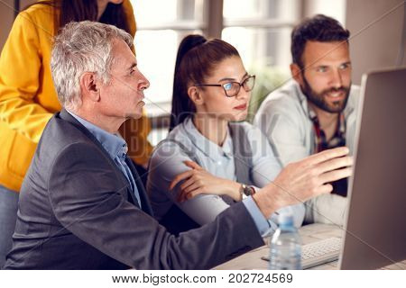 Senior manager gives suggestion to young business team