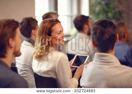 Profile of smiling woman with cell phone in audience on lecture on company meeting