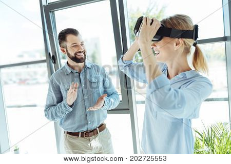 Pleased by result. Charming cheerful man giving applause to his upbeat young female colleague removing VR headset after its successful test