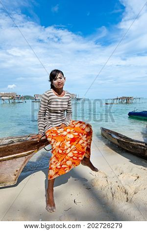 Semporna, Malaysia - April 17, 2015: Young Bajau Laut Girl Sitting On A Boat At The Shore Of Maiga I