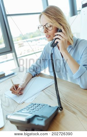 Always busy. Beautiful fair-haired businesswoman sitting at the table in her office, talking on the phone and making notes on the sheets of paper