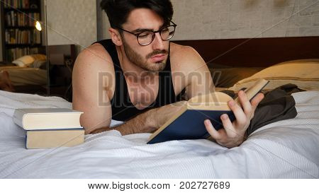 Young handsome man lying in bed and reading a book in his bedroom at home