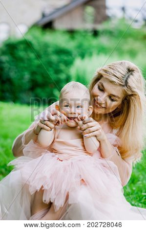 Woman in pink dress raises up her little daughter in the same clothes in the park with green grass