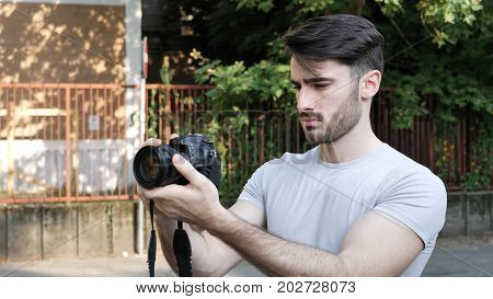 Handsome man holding photo camera and taking photo standing at street.