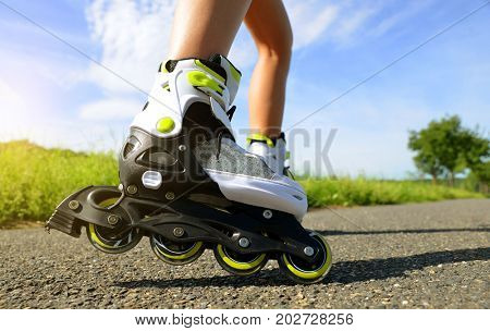 Female legs in inline skates in action outdoors on sunny day.