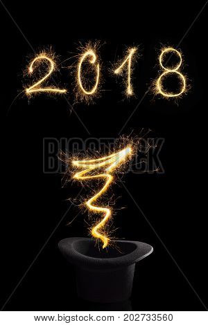 Magical new year. Magical fireworks from black top hat forming 2018 and abstract light lines isolated on black background. Happy new year background.
