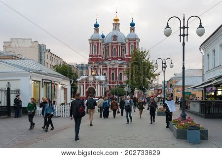 MOSCOW RUSSIA - AUGUST 29 2017: People walk along Clementovsky Street on summer evening. St Clement's Cathedral is in background.