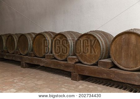 Old oak barrels lie in basement on wooden logs, old wine cellars with bottles and barrels