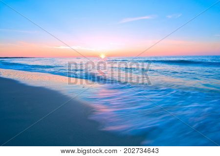 Sea waves and sunset. Blue sea landscape. Motion blur abstract picture.