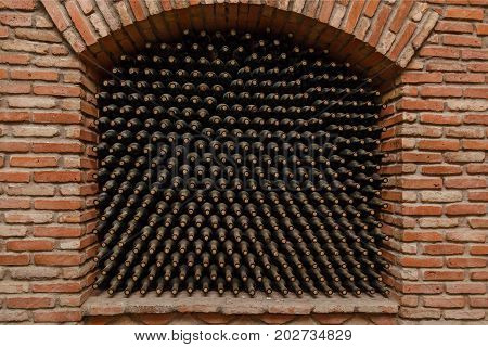Stacked up wine bottles in the cellar, old wine cellars with bottles and barrels