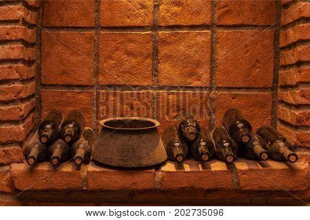 Winy bottles lie on bricks in basement, old wine cellars with bottles and barrels