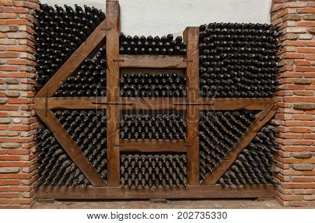 Winy bottles lie on shelving from thick logs, old wine cellars with bottles and barrels