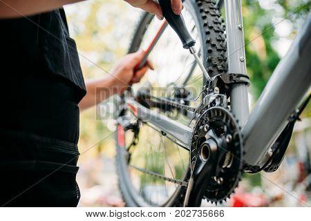 Hands with screwdriver repair shifter, bike repair