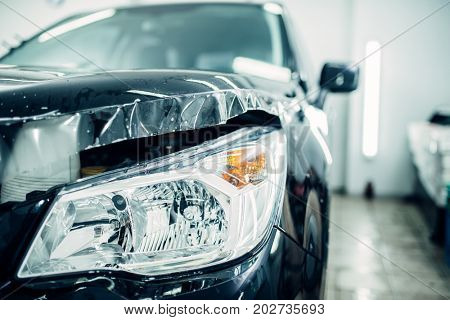 Car hood wraped in paint protection film closeup