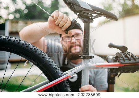 Bicycle mechanic adjusts with tools bike seat